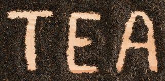 Słowo herbaty palec rysujący w stosie czarni herbaciani liście Zdjęcie Royalty Free