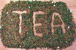 Słowo herbaty palec rysujący w stosie Japońska zielonej herbaty mieszanka z piec brown ryż Fotografia Stock