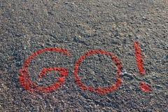 Słowo IŚĆ! pisać na asfalcie, ziemia Czerwony kolor kreda Zdjęcia Royalty Free