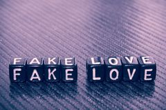 Słowo imitaci miłość czarni sześciany na zmroku zdjęcia stock