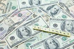 Słowo inwestycja na stosie dolarów amerykańskich banknoty obrazy royalty free