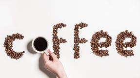 Słowo kawa robić od kawowych fasoli i ludzkiej ręki trzyma filiżankę czarna kawa Obrazy Royalty Free