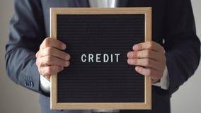 Słowo kredyt od listów na tekst desce w anonimowych biznesmen rękach zbiory wideo