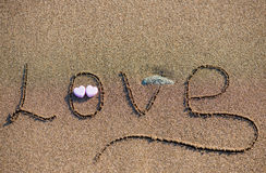Słowo miłość na piaska tle Fotografia Stock