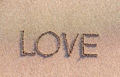 Słowo miłość na piaska tle Obrazy Royalty Free
