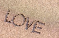 Słowo miłość na piaska tle Zdjęcie Royalty Free