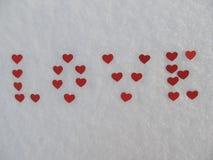 Słowo miłość od czerwonych serc w śniegu w zimie Zdjęcie Stock