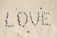 Słowo miłość pisać na piasku z morzem łuska przy zmierzchem na plaży Obrazy Royalty Free