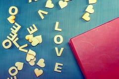 Słowo miłość pisać z drewnianymi listami na błękitnym tle złoty spinacz księgowego notatnik i piśmie czerwony taśmy Fotografia Royalty Free