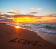 Słowo miłość na piaska zmierzchu plaży Obrazy Royalty Free