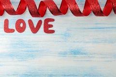 Słowo miłości czerwieni listy z czerwonym faborkiem na błękitnym drewnianym tle to walentynki dni miejsce tekst obrazy royalty free