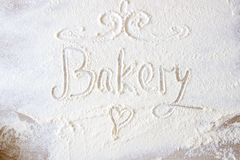 Słowo piekarni ręka pisać w mące na drewnianym stole ręki patroszony serce fotografia royalty free