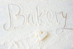 Słowo piekarni ręka pisać w mące na drewnianym stole tort w kształcie serca zdjęcia stock