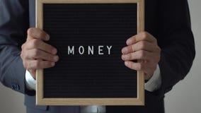 Słowo pieniądze od listów na tekst desce w Anonimowych biznesmen rękach zbiory