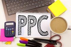 Słowo pisze PPC - Płaci na stuknięcie w biurze z laptopem, markier, pióro, materiały, kawa Biznesowy pojęcie dla interneta SEO Mo Obrazy Stock
