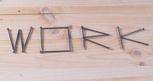 Słowo praca pisać z gwoździami Fotografia Stock