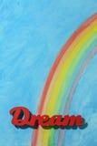 Słowo sen z kolorowym tęczy i niebieskiego nieba tłem Zdjęcie Royalty Free