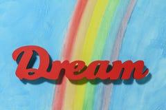 Słowo sen z kolorowym tęczy i niebieskiego nieba tłem Zdjęcie Stock