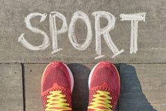 Słowo sport pisać na szarym bruku z kobietą iść na piechotę w sneakers, widok z góry obrazy royalty free