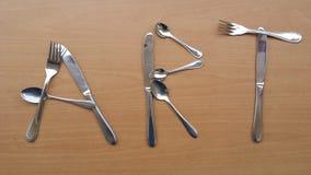 Słowo sztuka z metalem rozwidla łyżki i knifes Zdjęcie Royalty Free