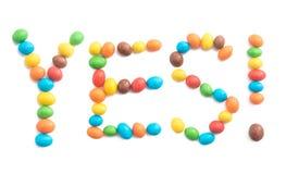 Słowo Tak z kolorowego cukierku odizolowywającego na białym tle Fotografia Stock