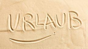 Słowo Urlaub pisać w złotym plażowym piasku Fotografia Royalty Free