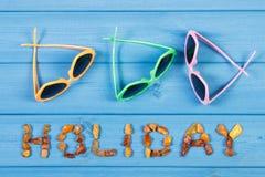 Słowo wakacje robić bursztynów okulary przeciwsłoneczni i kamienie na błękitnych deskach, lato czas obrazy stock