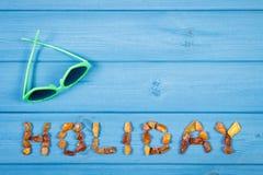 Słowo wakacje robić bursztynów okulary przeciwsłoneczni i kamienie na błękitnych deskach, lato czas, kopii przestrzeń dla teksta zdjęcia royalty free