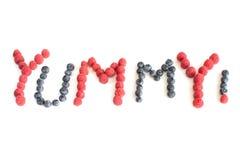 Słowo Yummy! pisać w malinkach i czarnych jagodach Obraz Royalty Free