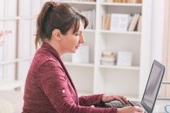 Słuchać - nadwyrężona kobieta pracuje z laptopem obraz royalty free