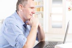 Słuchać - nadwyrężony mężczyzna pracuje z laptopem Zdjęcie Royalty Free