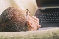 Słuchać - nadwyrężony mężczyzna używa laptop Obrazy Royalty Free