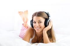 Słuchająca muzyka na łóżku Obrazy Royalty Free