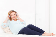 słuchający muzyczny kobieta w ciąży zdjęcie royalty free
