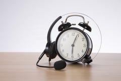 Słuchawki coiled nad retro budzikiem fotografia stock