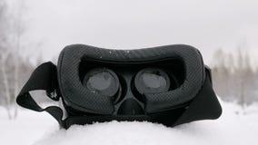 Słuchawki rzeczywistość wirtualna kłama na śniegu w lesie Je ` s snowing Obiektyw kamera zbiory