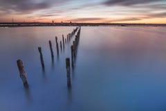 Słupy w wodzie na zmierzchu oceanie i chmurach - Obraz Royalty Free