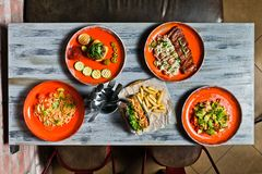 Słuzyć stół z różnorodnymi naczyniami restauracja Hot dog, grill wieprzowiny ziobro, stek, Carbonara pasta i krab sałatka, zdjęcia stock
