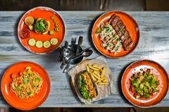 Słuzyć stół z różnorodnymi naczyniami restauracja Hot dog, grill wieprzowiny ziobro, stek, Carbonara pasta i krab sałatka, fotografia royalty free