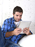30s使用数字式片剂垫的人在家说谎在看起来长沙发的网络放松 免版税库存照片