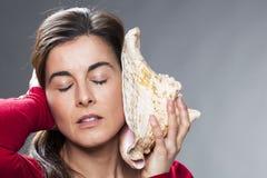 30s听从巨型壳的海洋声音的深色的妇女 库存图片
