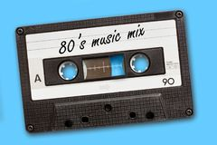 80 ` s在葡萄酒卡型盒式录音机磁带写的音乐混合,蓝色背景 图库摄影