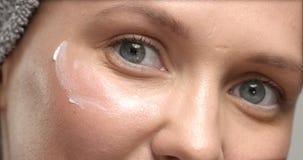 30 ` s妇女与眼睛奶油按摩的` s eue特写镜头它和摩擦它 库存照片
