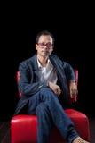 45s岁亚裔人的画象面孔坐红色沙发  免版税库存图片