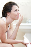 30s应用润湿的奶油的妇女 库存照片