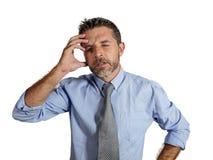 30s或40s在劳累过度衬衣和领带遭受的头疼的感觉的可爱的被用尽的和被注重的商人和 免版税库存照片