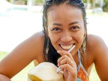 30s或40s愉快和可爱的亚裔印度尼西亚妇女生活方式自然画象在比基尼泳装饮用的椰子水中在热带 免版税图库摄影