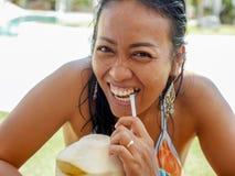 30s或40s愉快和可爱的亚裔印度尼西亚妇女生活方式自然画象在比基尼泳装饮用的椰子水中在热带 库存图片
