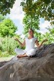 20s放松在岩石的一棵树下的白肤金发的女孩 库存照片