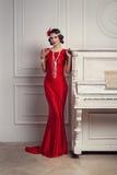 20 ` s的红色礼服样式的年轻美丽的女孩或30 `与杯的s在钢琴附近的马蒂尼鸡尾酒 葡萄酒样式美丽的妇女 库存图片